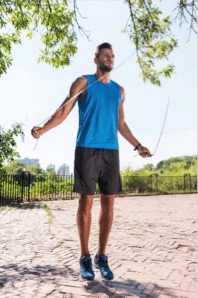 Homme faisant sa routine de corde à sauter en extérieur pendant ses vacances