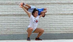 femme faisant un overheadsquat avec son petit frère